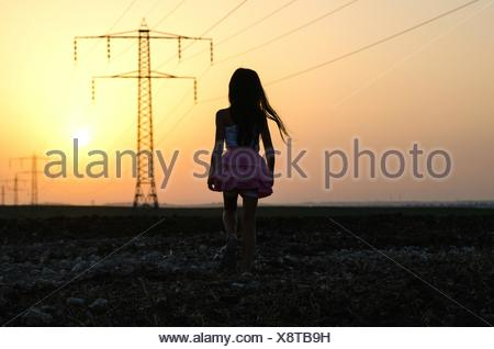 Rear View Of Girl Walking On Field Against Sunset Sky - Stock Photo