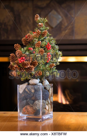 Infront of a Glowing fireplace sits a decorated furtree with cones and berries in a glass vase filled with stones on a table - Stock Photo