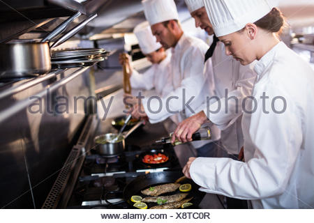 Chef frying fish in a frying pan - Stock Photo