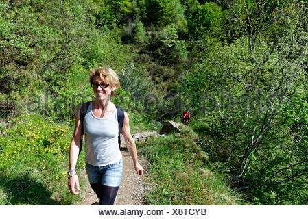 Mature female hiker hiking up hillside path - Stock Photo