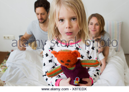 Portrait of sullen young girl on her parents bed - Stock Photo
