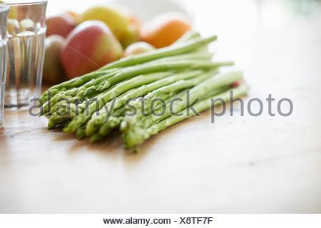 Asparagus, fruits, drinking glass on dining table