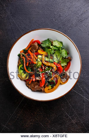 Szechuan beef stir fry with vegetables in bowl on dark background - Stock Photo