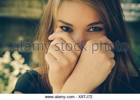 Portrait Of Young Woman Looking From Behind Fist - Stock Photo