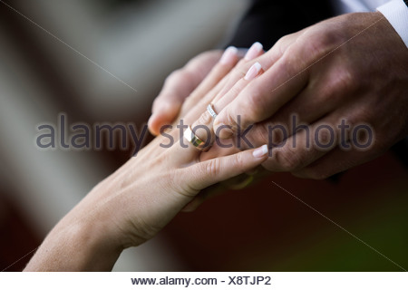 Bridegroom and bride putting on rings - Stock Photo