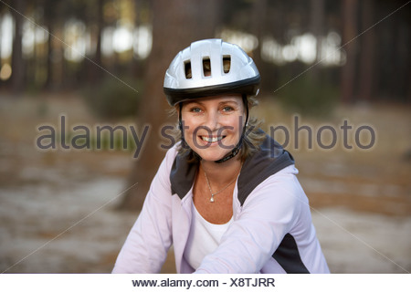 Woman wearing cycling helmet and pink hooded sports top smiling close up portrait - Stock Photo