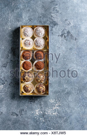 Variety of homemade dark chocolate truffles with cocoa powder, coconut, walnuts in golden gift box over blue texture background. Top view, copy space. - Stock Photo