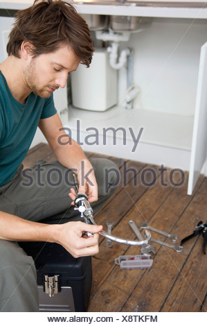 Mid adult man repairing a faucet in the kitchen - Stock Photo