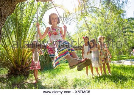 Girls queueing for tree swing in garden - Stock Photo