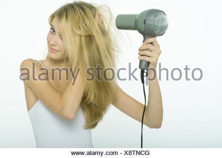 Teenage girl blow-drying hair - Stock Photo