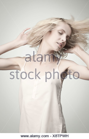 Young woman tossing hair with eyes closed, portrait - Stock Photo