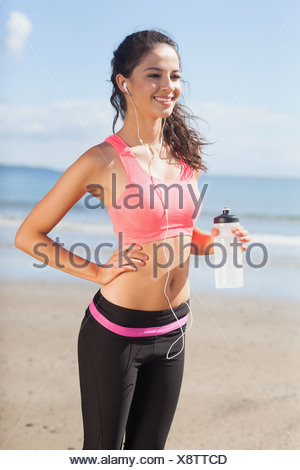 Beautiful smiling healthy woman holding water bottle on beach - Stock Photo