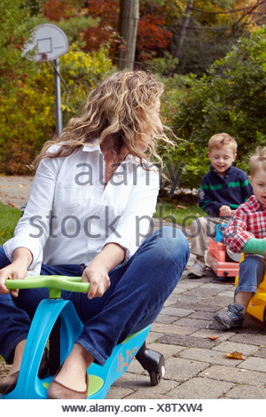Mother and young sons riding on toy cars in garden - Stock Photo