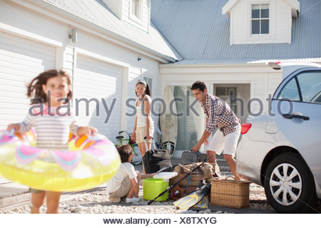 Girl with inflatable ring running in driveway - Stock Photo