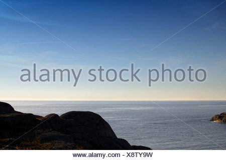 Scenic shot of rocks with peaceful sea against the clear sky - Stock Photo