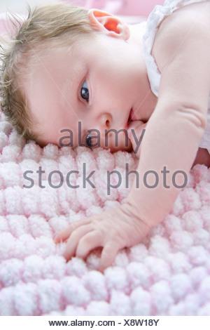 Baby girl lying on side sucking finger - Stock Photo