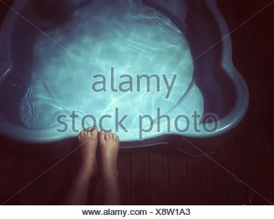 Close-up of a girl's feet on the edge of a paddling pool - Stock Photo