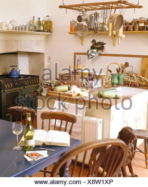 Utensils on hanging rack above island unit with sink in cottage kitchen with range oven and blue painted table - Stock Photo
