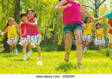Children running on grass - Stock Photo