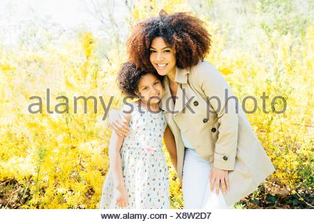 Portrait of mother with arm around daughter, looking at camera, smiling - Stock Photo