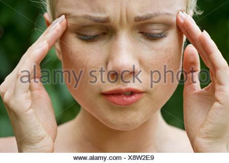 Woman rubbing temples - Stock Photo
