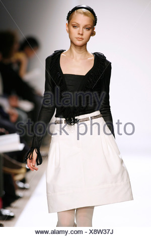 Anne Klein New York Ready to Wear Autumn Winter Model wearing white volume skirt, black long sleeve top fringed cuffs and v - Stock Photo