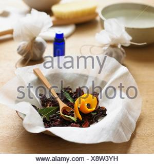 Dried rosehip, hibiscus, cloves, juniper berries, bay leaves, orange peel in bowl lined with muslin, tied-up muslin bags and bottle of ginger essential oil in the background (making a foot soak) - Stock Photo