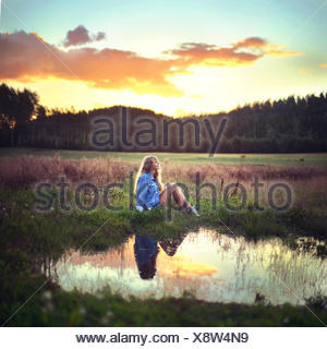 Young woman sitting by water - Stock Photo