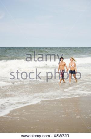 Couple walking in ocean surf - Stock Photo