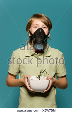 Boy wearing gas mask, holding wilted potted plant - Stock Photo