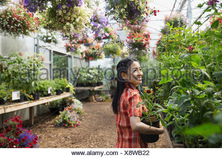 Smiling woman with flowers in plant nursery greenhouse - Stock Photo