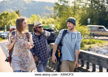 Three people walking together carrying backpacks, smiling - Stock Photo