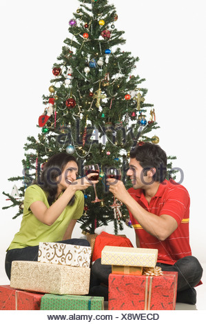 Couple toasting with wine glasses in front of a Christmas tree - Stock Photo
