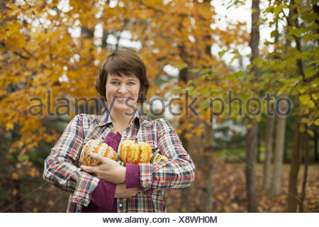 Organic farm A woman holding an armful of large squash vegetables - Stock Photo