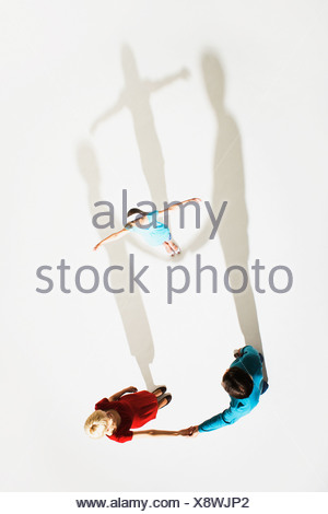 Couple and young girl standing so shadows look like they're holding her up high - Stock Photo