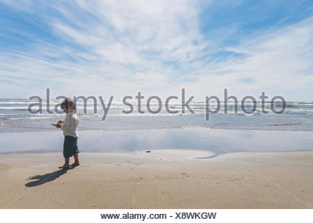 Boy standing on beach holding a crab - Stock Photo