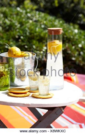 Limoncello soda in glass carafe and ice bucket of lemons on table - Stock Photo