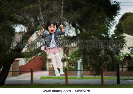Girl playing on swing in park