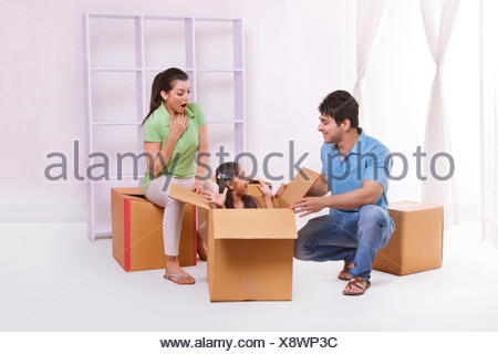 Girl playing hide and seek with parents - Stock Photo