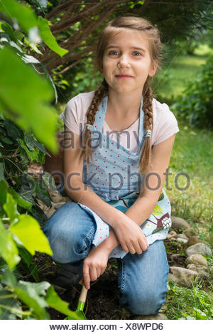 Portrait of girl with pigtails gardening - Stock Photo