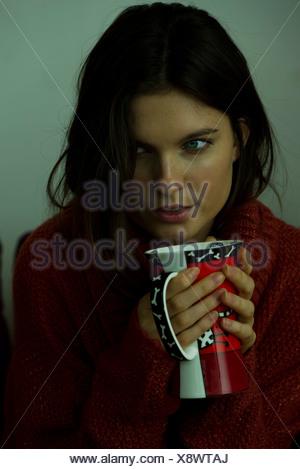 Woman in sweater holding mug, portrait - Stock Photo
