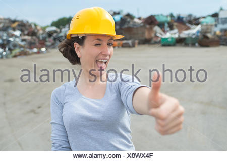 happy female worker with thumbs-up in a car scrap yard - Stock Photo