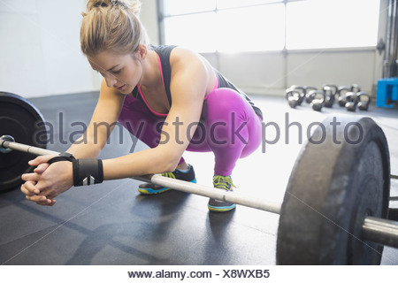 Woman leaning on barbell - Stock Photo