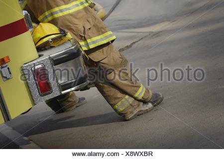 Firemen leaning against fire truck - Stock Photo