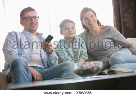 Boy watching TV with parents in living room - Stock Photo