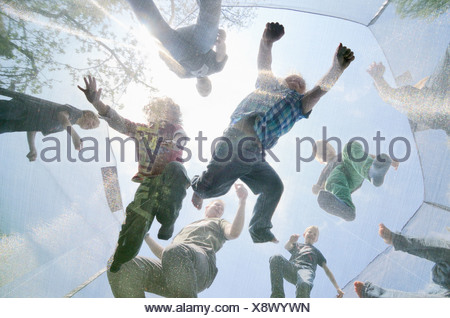 Mature men and boys jumping on trampoline, low angle view - Stock Photo