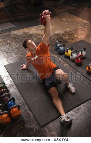 Bodybuilder lifting kettlebell in gym - Stock Photo