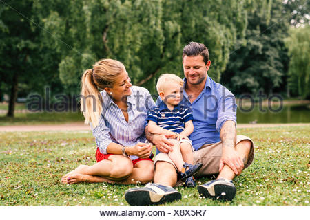 Parents watching son while sitting at park - Stock Photo