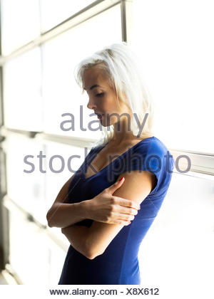 Woman standing by window - Stock Photo
