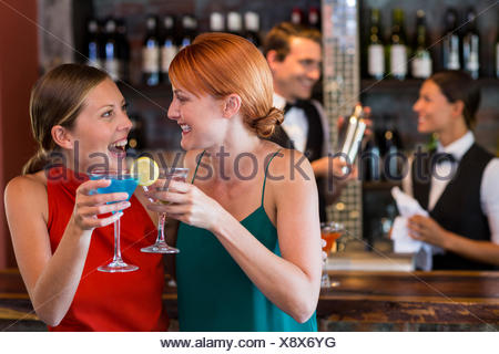 Friends holding a cocktail in front of bar counter - Stock Photo